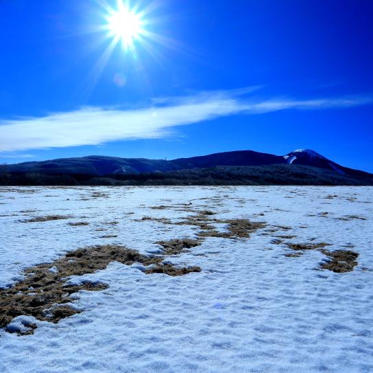 残雪の蓼科牧場に太陽