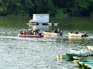 ボートで事故現場へ向かう捜査員
