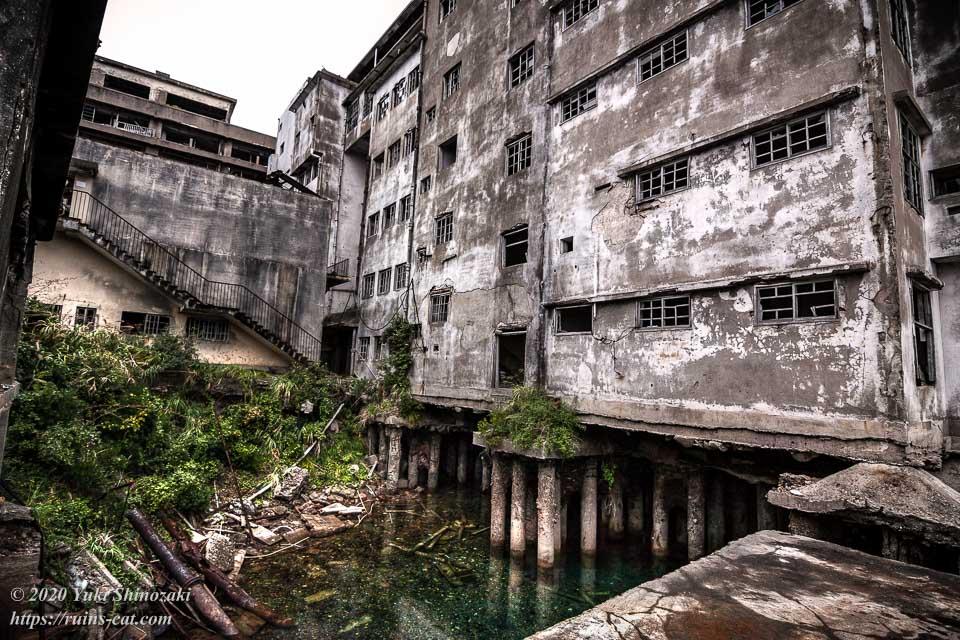 端島小中学校の裏手。陥没した穴の中、建物の円柱状の基礎の下には陥没した穴には海水が入り込んでいる。