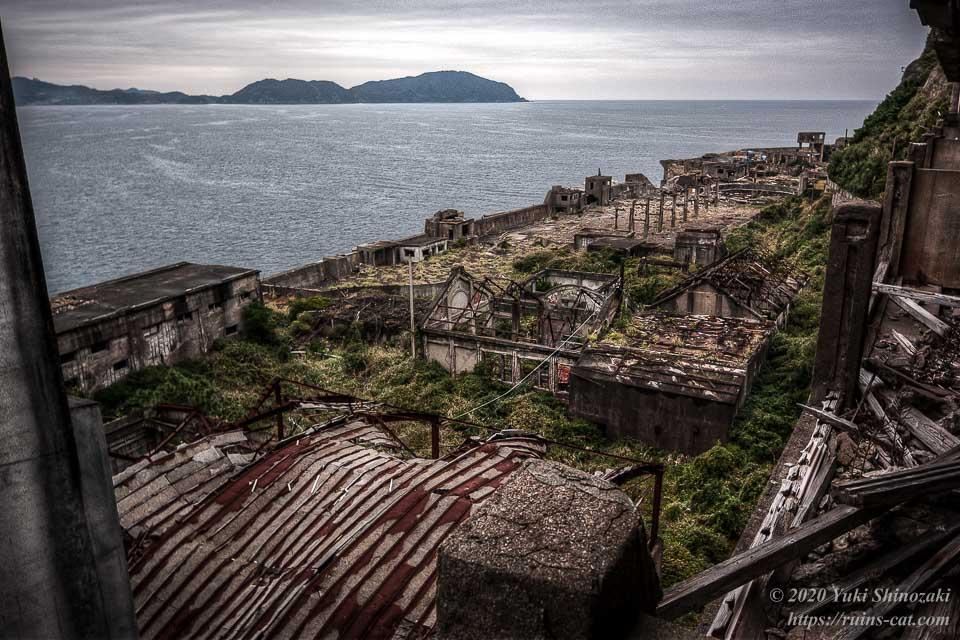 発電所や貯炭場など炭鉱用設備が集まっている場所を65号棟上階より俯瞰する。海の向こうには長崎の先端、野母崎が見える。