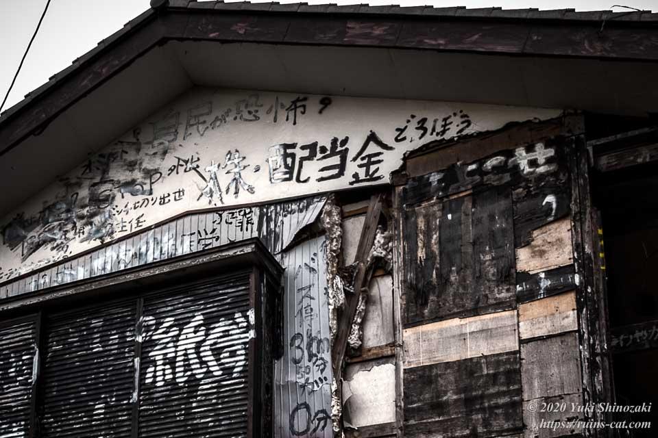 黒い家の2階の西側の軒下には「自民が恐怖」「株・配当金どろぼう」などと書かれている