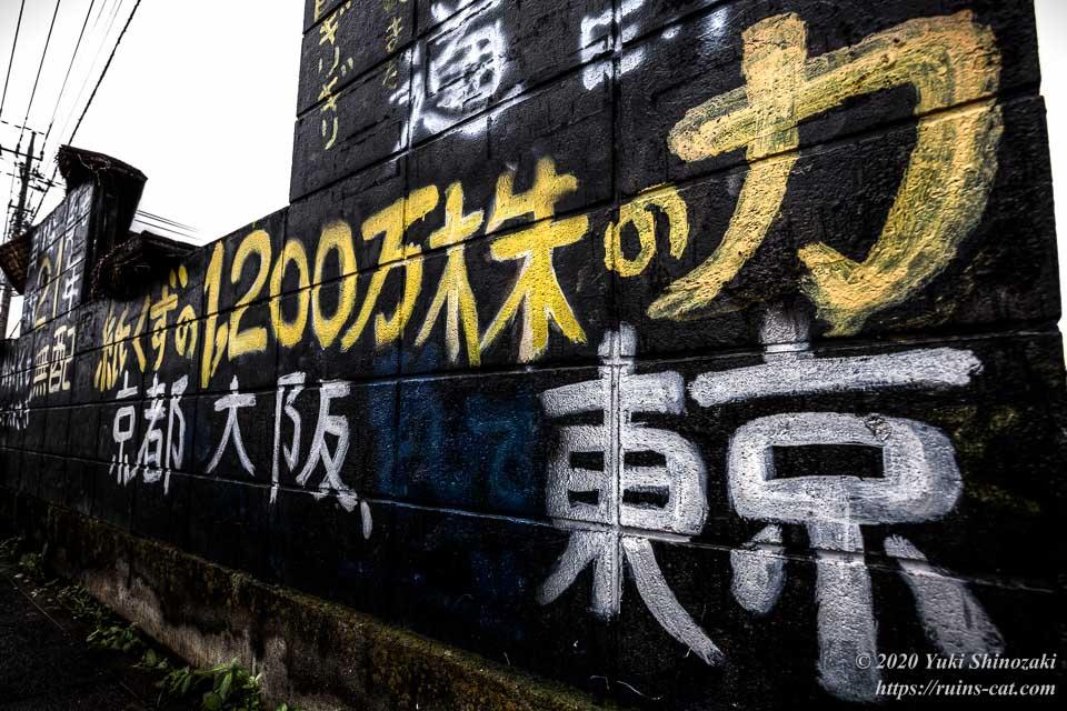 黒い家の黒い壁には黄色い文字で「紙くずの1,200万株の力」と落書きされている
