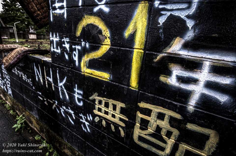 「21年無配」「NHKもニュースでさぎ」などと書かれた塀の落書き