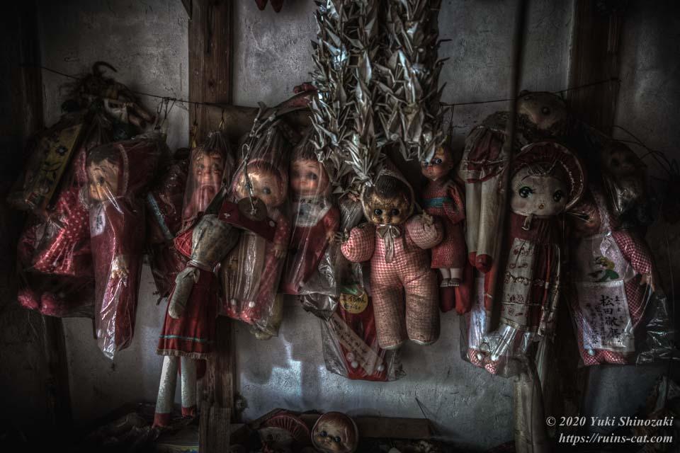 壁にくくりつけられた人形たち