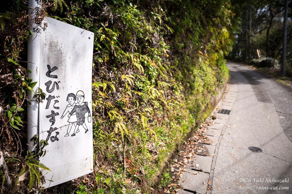 通学路の脇にあった注意喚起の看板「とびだすな」。色はすっかり抜け落ちてしまっている。