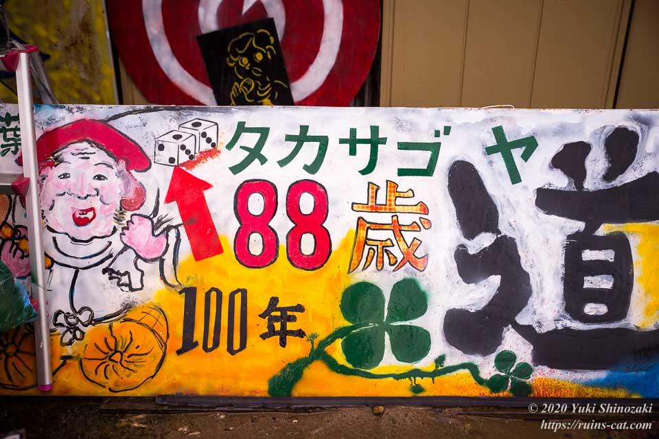「タカサゴヤ・88歳・100年・大黒様・道」と書かれた看板