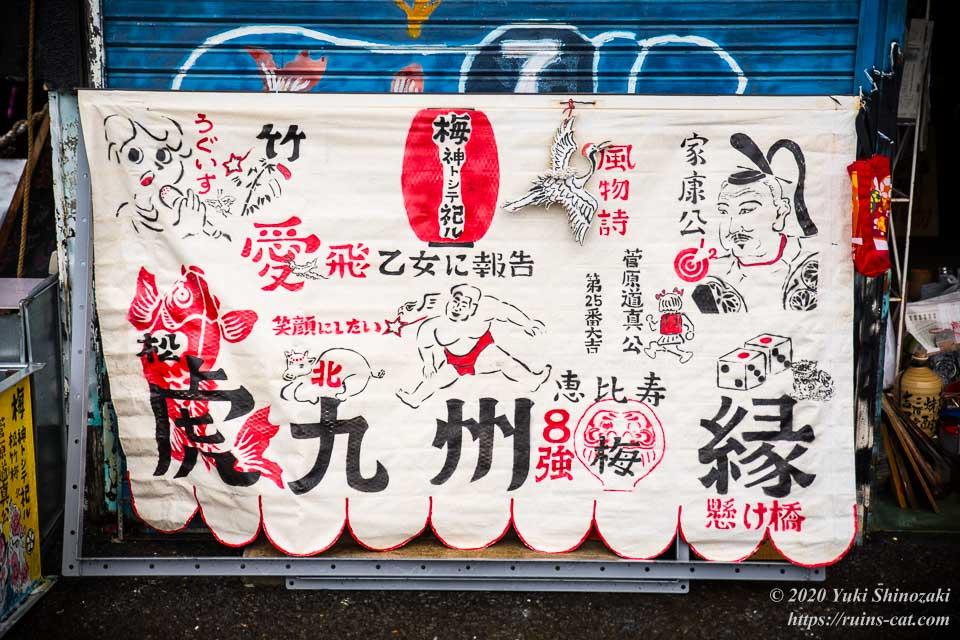 店の正面に掲げてある白布には「梅神トシテ祀ル」と書かれた赤い提灯や相撲取り、家康公などが描かれている
