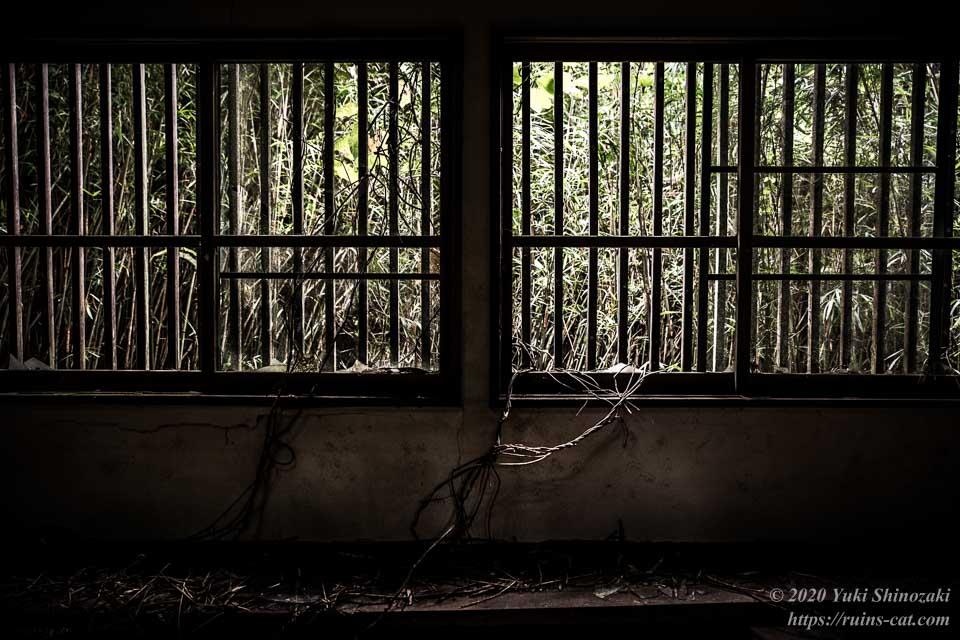 小川脳病院(心霊スポット) 隔離病棟の大部屋の窓にはめ込まれた堅牢な格子が、部屋の中に暗く重い影を投げかける。