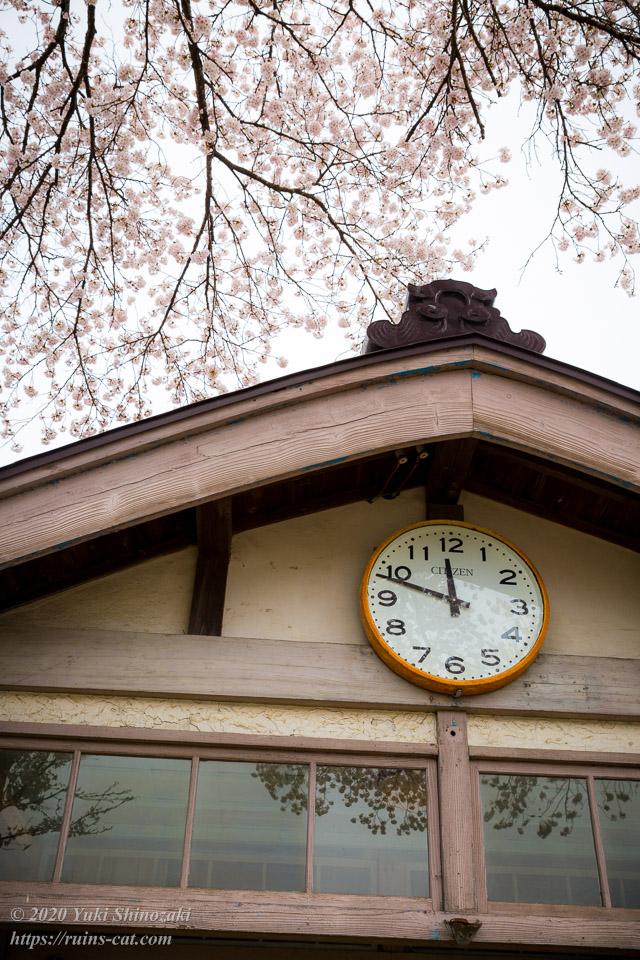 昇降口の時計と桜