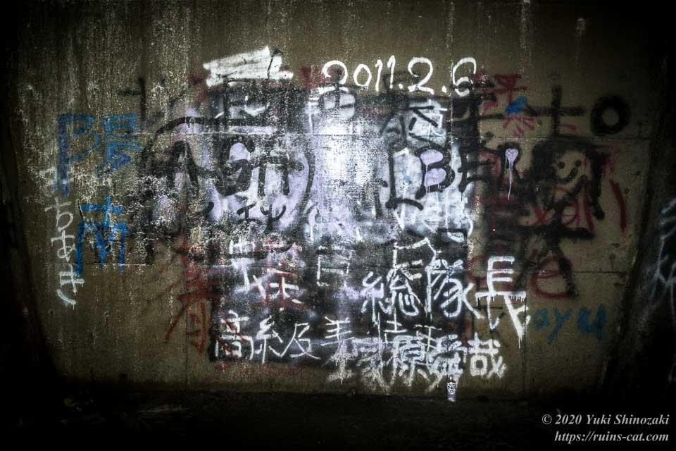 矢板トンネルを塞いでいる一番奥の壁のクローズアップ。落書きが幾層にも重ねられていて判読が難しいが、右下には「総隊長 塚原舜哉」の文字が読み取れる。