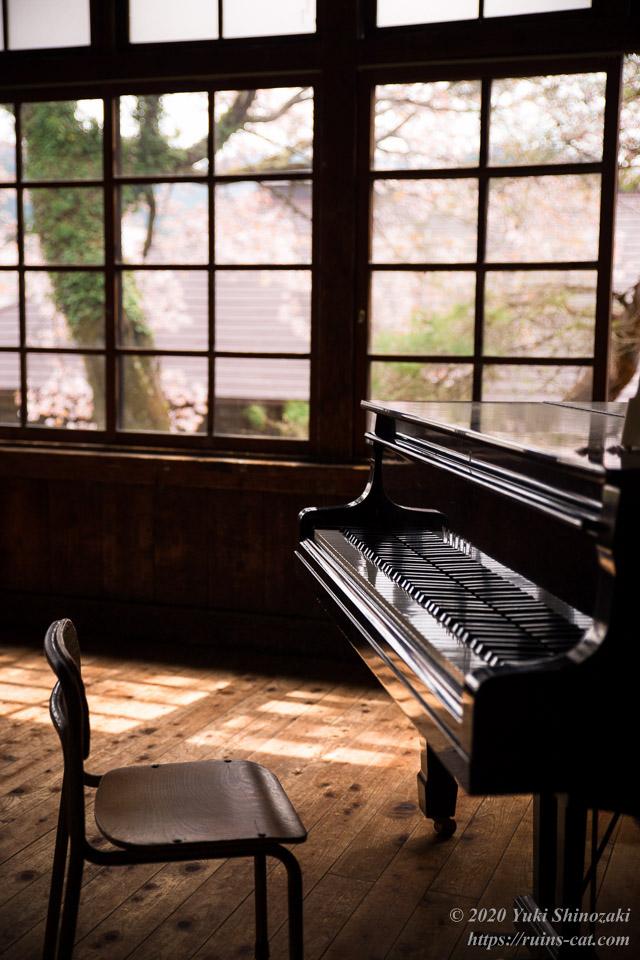 春の陽が差し込む音楽室。ピアノの鍵盤には陽光が反射している。窓の外は満開の桜だ。