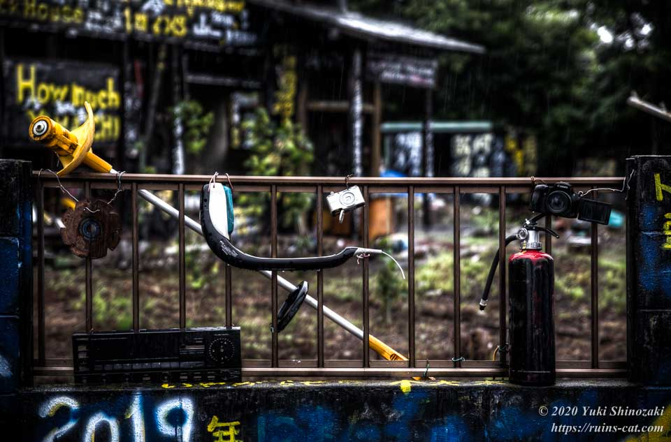 シャワーホースの頭・消化器・デジカメ・分解された草刈り機・オーディオなどが括り付けられた塀