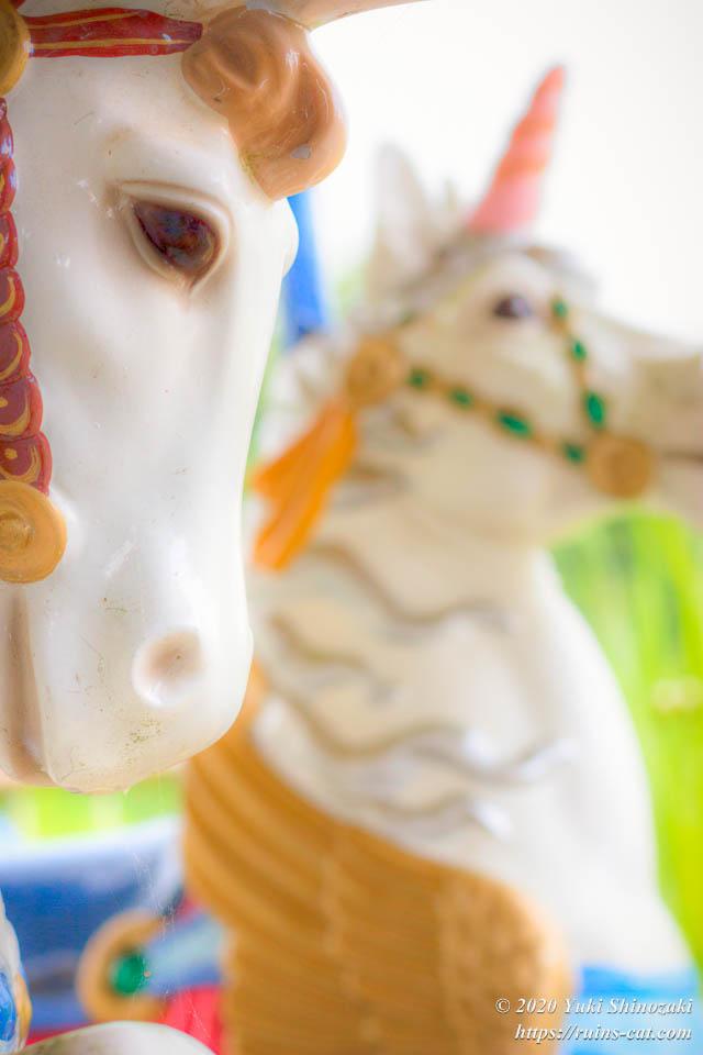 メリーゴーランドの白馬と白いユニコーン