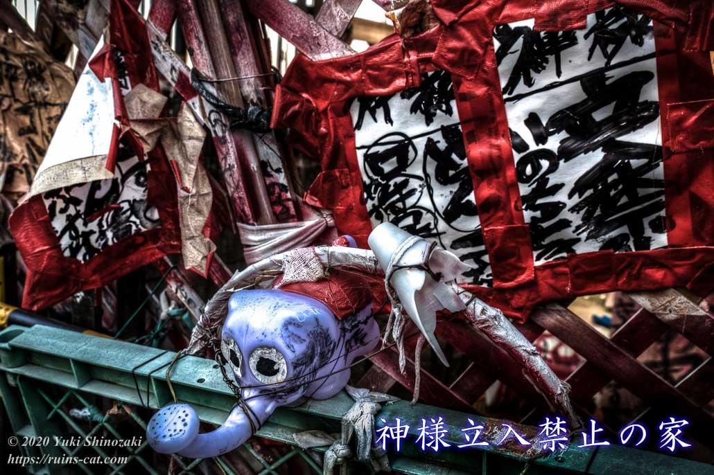 神様立ち入り禁止の家(静岡県浜松市・電波物件) 出入口はバリケードで塞がれ、象さんのジョーロがくくり付けられている。「神様」「立入禁止」「いのちとる」などと書かれている。