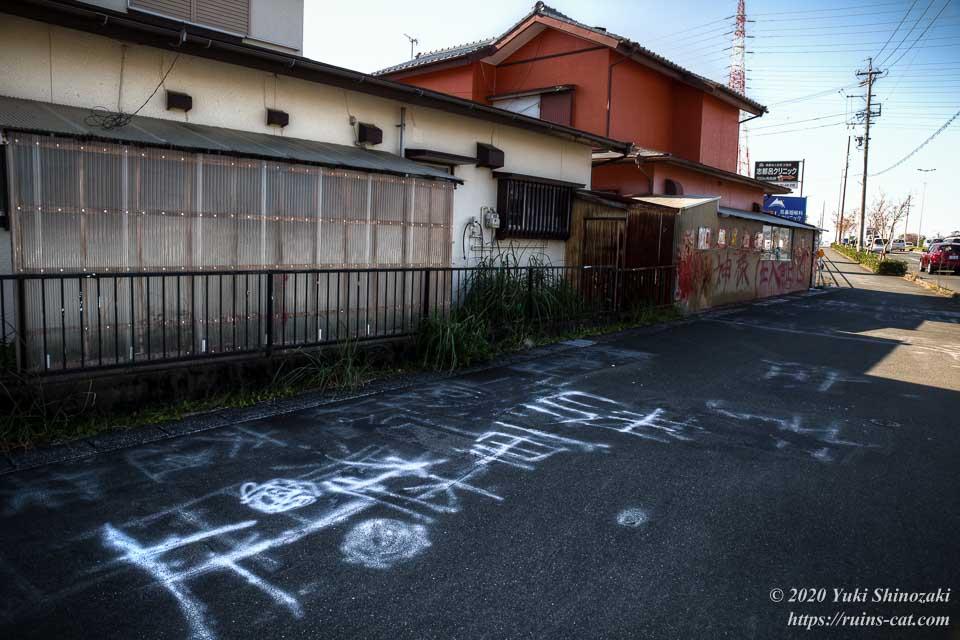 神様立ち入り禁止の家と、歩道に落書きされた「駐車禁止」の文字
