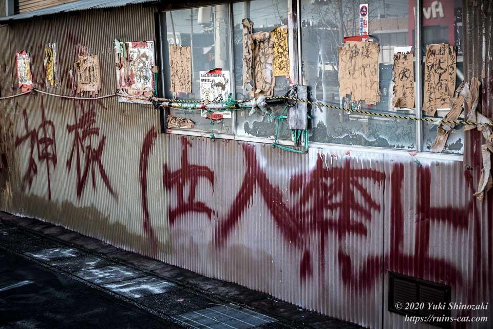 「神様(立入禁止)」の赤い落書きと様々なガムテープの張り紙