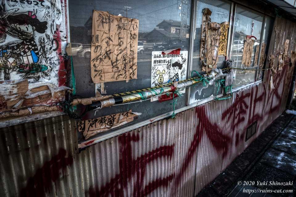 県道62号線側の壁にはガムテープが貼り付けられ、その上に「神様見てる」「いのちとる」などと書かれている。