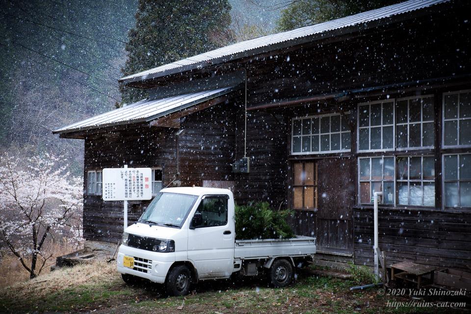 池津川小学校 旧校舎。入口の前には軽トラが停まっており、中では人が何か忙しく作業をしている。