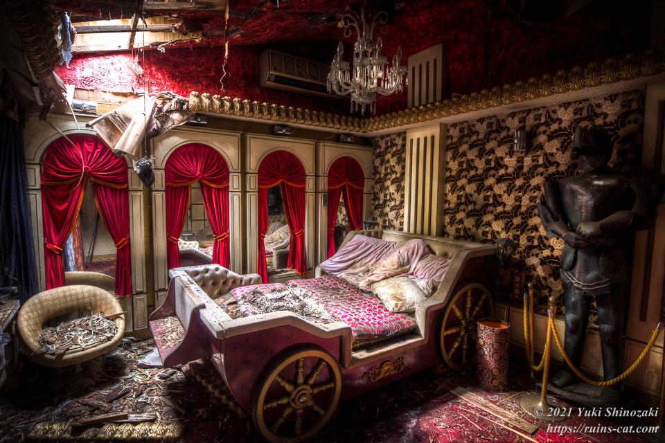 モーテル風林 和室「葵」 馬車風ベッドの周りをレッドカーテンとプレートメイルが飾っている