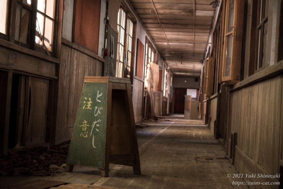 小倉沢小中学校の2階廊下には「とびだし注意」と書かれた四角錐状の看板が残されていた