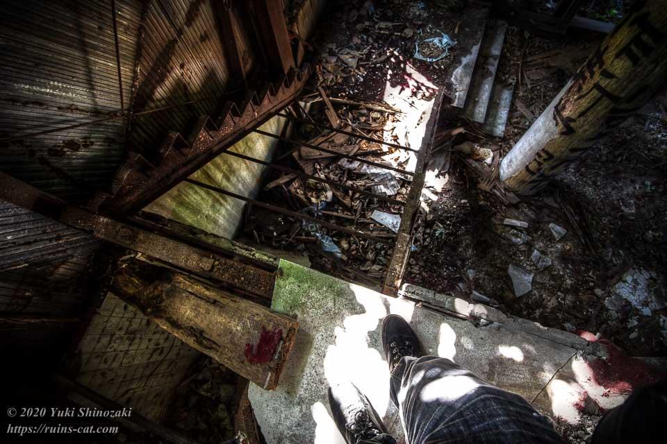 踏み板のなくなった階段を慎重に降りていく筆者