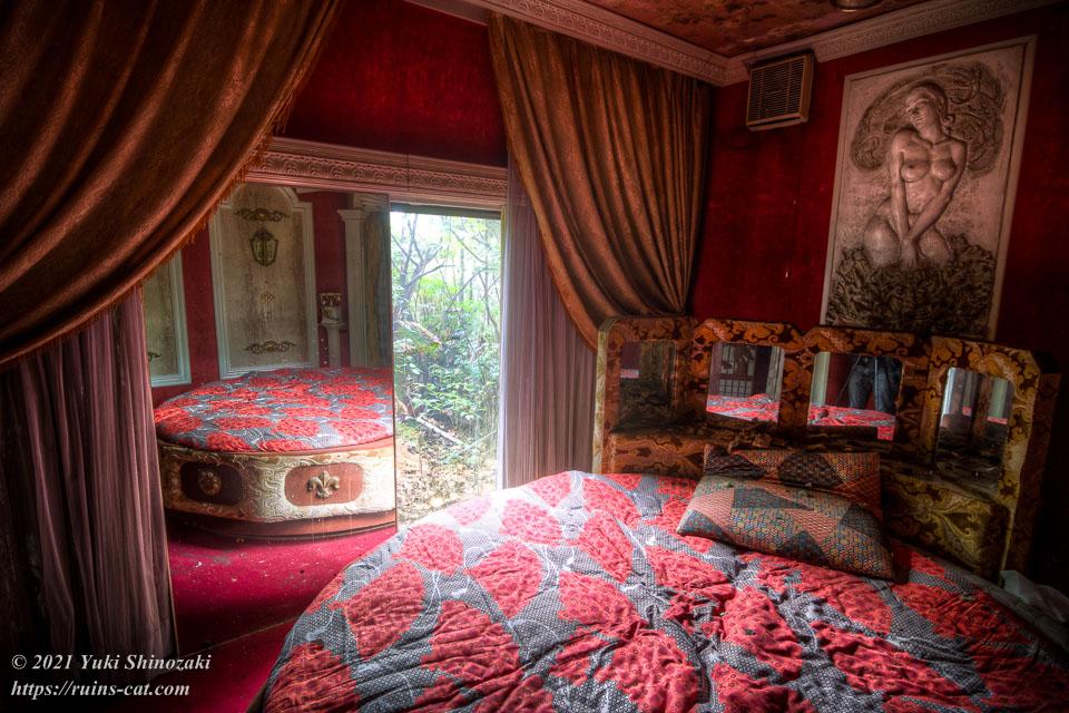 モーテル風林 デラックス洋室「蘭」の回転ベッドとベッド脇の巨大な鏡、壁のレリーフ