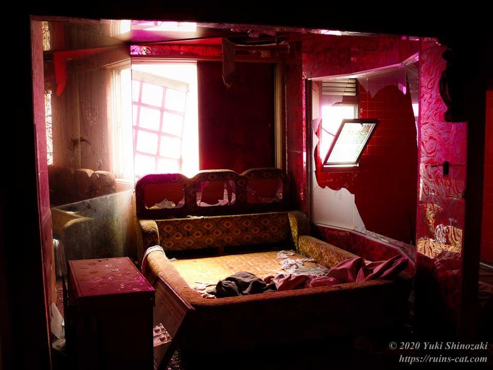 ホテルセリーヌ(心霊スポット)の赤く彩られた客室。中央にはベッドが置かれ、風呂場との間を仕切るガラス窓は割られている。