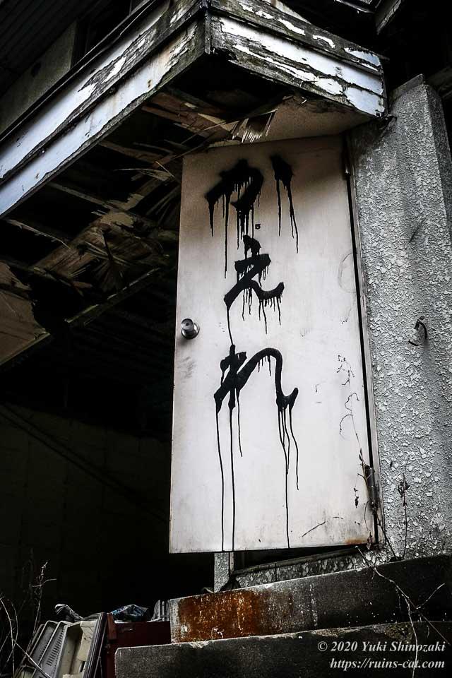 ホテルセリーヌの階段のドアに書かれた「かえれ」の警告