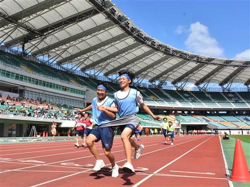 2人一組の「デカパン競走」で息を合わせて走る生徒=13日午前、袋井市のエコパスタジアム